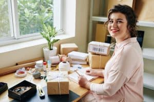 Pretty smiling woman working in her home office, wrapping packages and writing in planner